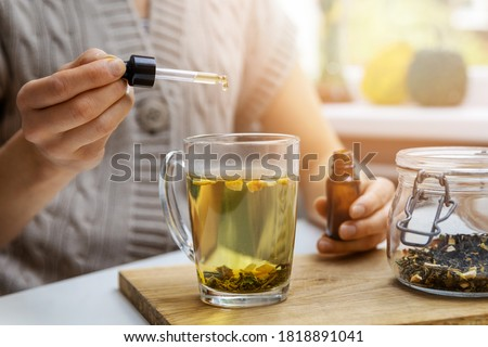 dietary supplements and vitamins - woman adding drop of cbd oil in cup of tea with pipette. anti stress