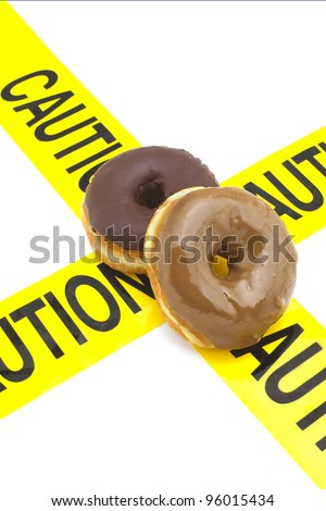 Dietary warning, or high calorie/high, fat junk food warning (donuts placed on top of yellow caution tape)