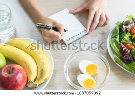 Dieting and calories control for wellness. Woman using smartphone calculate calories of food in breakfast during dieting for lose weight program and take notes.