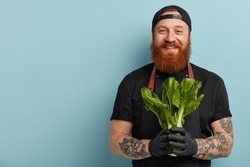 Dieting and healthy eating concept. Cheerful male chef holds green salad, shares recipe of vegetarian dish, supports healthy ration, says eat vegetables which contain vitamins, likes cooking process