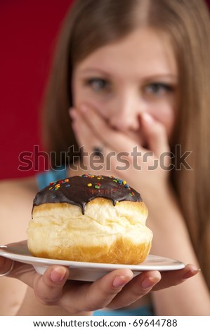 Dieting concept: attractive girl with doughnut closing her mouth by hand. Doughnut in focus, face unfocused