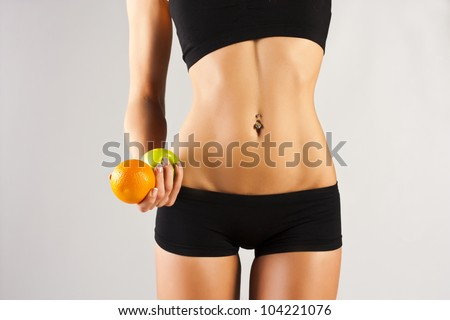 Dieting concept, Beautiful belly and a fruit isolated on grey