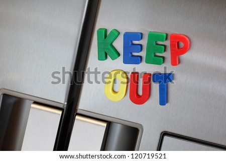 Dieting concept the words keep out spelled in fridge magnet letters on a refrigerator door