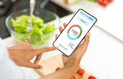 Dieting Concept. Unrecognizable woman eating vegetable salad and counting daily calories with app on smartphone, checking calorie chart in mobile application, creative collage for weightloss, closeup
