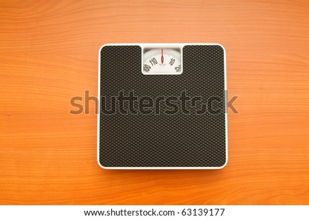 Dieting concept with scales on the wooden floor