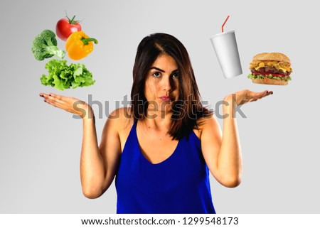 Dieting concept, young woman choosing between healthy food and junk food. Health vs unhealthy. #1299548173