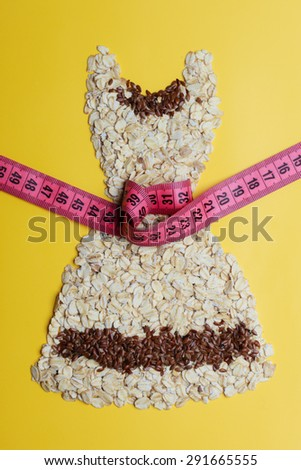 Dieting healthy eating slim down concept. Female dress shape made from oatmeal flax seeds with measuring tape around thin waist on yellow