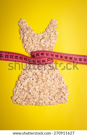Dieting healthy eating slim down concept. Female dress shape made from oatmeal with measuring tape around thin waist on yellow