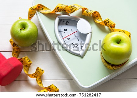 Dietitian use Green apple with weight scale and measuring tape for the healthy diet slimming . Diet and Healthy Concept #751282417