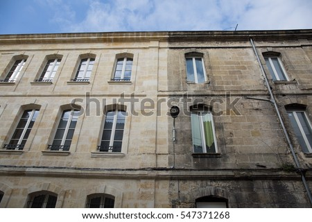 Difference between a wash cleaned house facade and a dirty one in a cit, before and after #547371268