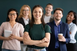 Different age and ethnicity businesspeople standing behind of female company chief business owner with hands crossed posture of confident independent businesswoman leader of multi-ethnic team concept