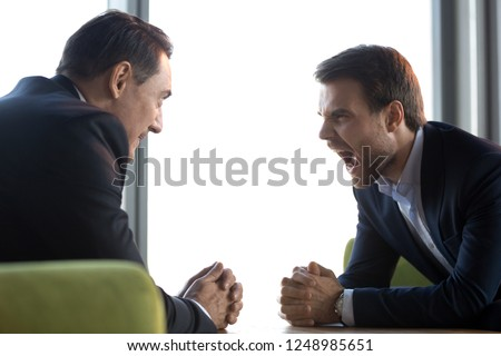 Different aged businessmen sitting on couch in office room face to face staring to each other. Millennial man looking at senior male screaming showing expressing aggression unfriendliness animosity