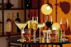 Different alcohol drinks on table in bar