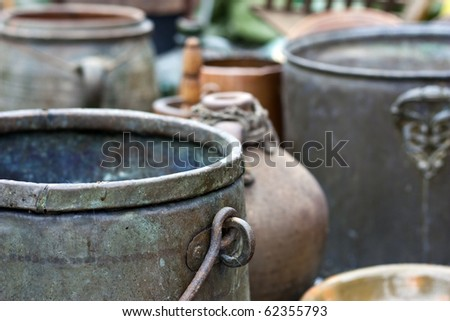 Different ancient iron and clay kettles and pots