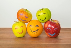 Different apples and orange with funny faces, tolerance, originality or friendship concept.