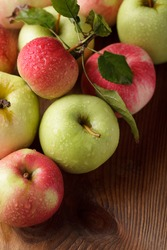 Different apples on wooden table in garden