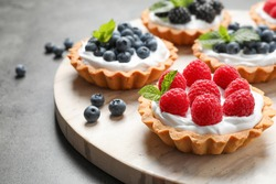 Different berry tarts on light table. Delicious pastries