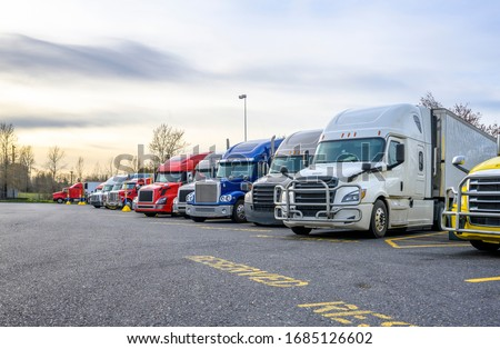 Different big rigs semi trucks with semi trailers standing in row on truck stop parking lot with reserved spots for truck driver rest and compliance with established truck driving regulations