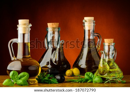 different bottles of infused olive oil with fresh green herbs