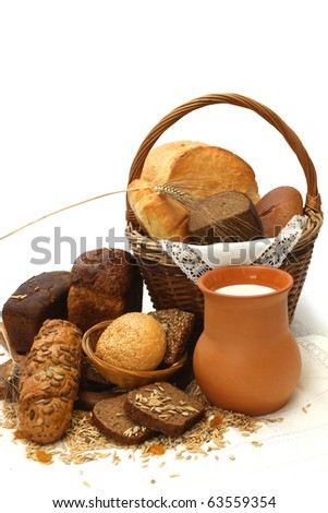 Different bread products with jug of milk on white background
