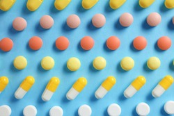 Different bright pills on color background, flat lay