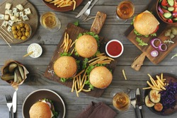 Different burgers with snacks and wine on the wooden table, top view. Outdoors food Concept