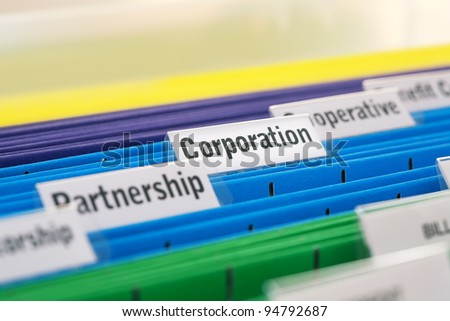 Different business organizations filed in colored folders, focus