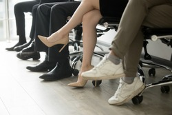 Different business people sitting in row, men and women waiting in queue line for job interview with lady in high-heeled shoes in focus, human resources, employment hiring concept, legs close up view