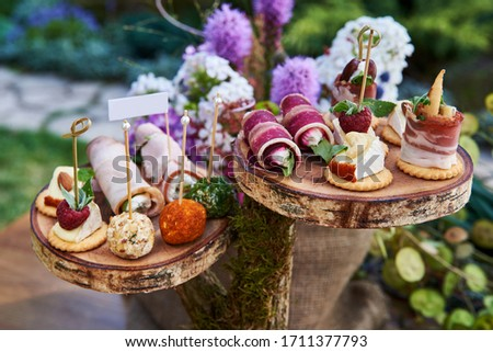 Different canapes with smoked salmon, cucumber, tomatoes, cheese, meat. Breakfast buffet table with a variety of snacks. Buffet served table with snacks,fruits,canape,sweets and appetizers. Photo stock ©