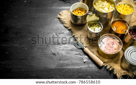 Different canned products in tin cans. On the black chalkboard.