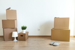 Different cardboard boxes for moving at room interior movement or delivery concept, empty wall  with copy space for your text
