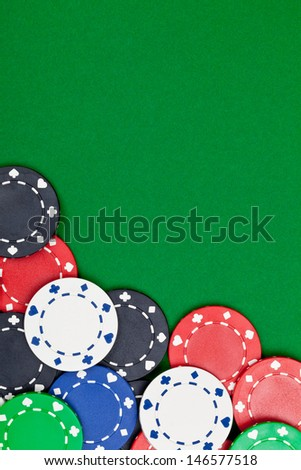 Different casino chips on green table background with copyspace