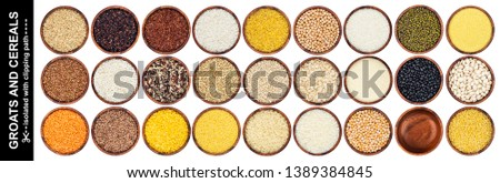 Different cereals, grains and flakes isolated on white background with clipping path, assortment of groats in wooden bowls, top view