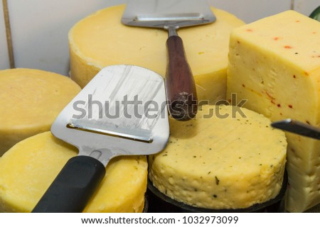Different  cheese on a tray round and square with two cheese slicer, ostehovel, osthyvel, on top