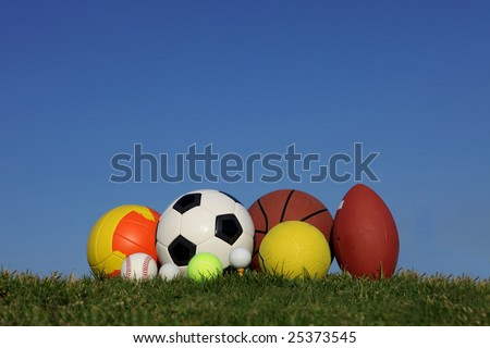 different children\'s sports balls outside on lawn
