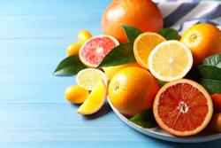 Different citrus fruits on light blue wooden table, closeup