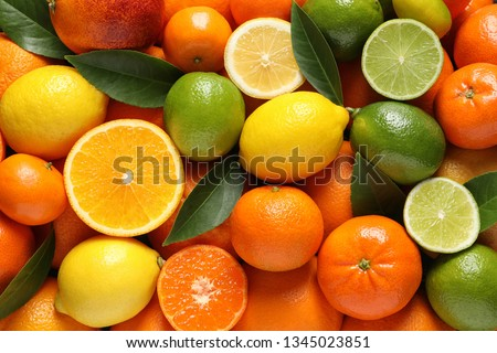 Different citrus fruits with leaves as background, top view #1345023851