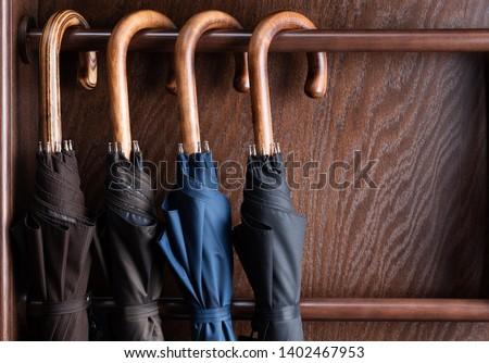 Different classic wooden handle walking length umbrellas on display in luxury clothing boutique store. #1402467953