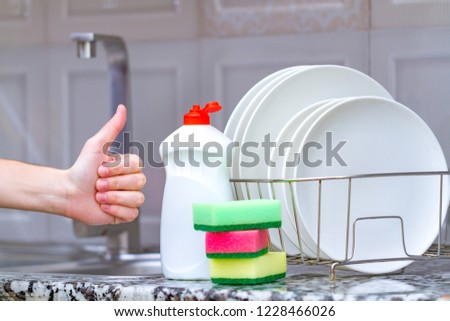 Different clean plates in dish drying rack, dish sponges and dishwashing detergent on the table on kitchen counter. Clean dishes
