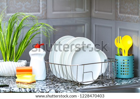 Different clean plates in dish drying rack, dish sponges and dishwashing detergent on the table on kitchen counter. Washing dirty dishes