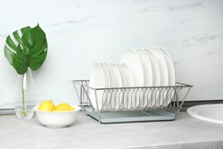 Different clean plates in dish drying rack on kitchen counter