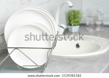 Different clean plates in dish drying rack on kitchen counter - Shutterstock ID 1139381582