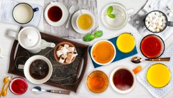 Different cold and hot drinks on wooden table. Tea, milk, juice,coffee, smoothie, water, pot, tray and tissue. Concepts of healthy traditional tasty drinks.