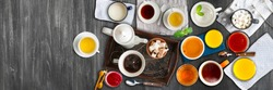 Different cold and hot drinks on wooden table. Tea, milk, juice,coffee, smoothie, water, pot, tray and tissue. Concepts of healthy traditional tasty drinks. Wide panoramic image. Horizontal banner