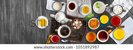 Different cold and hot drinks on wooden table. Tea, milk, juice,coffee, smoothie, water, pot, tray and tissue. Concepts of healthy traditional tasty drinks. Wide panoramic image. Horizontal banner #1051892987