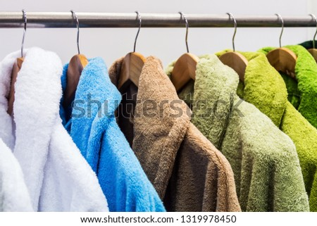 different color bathrobes on the hanger in the shower room, in the store or on the market