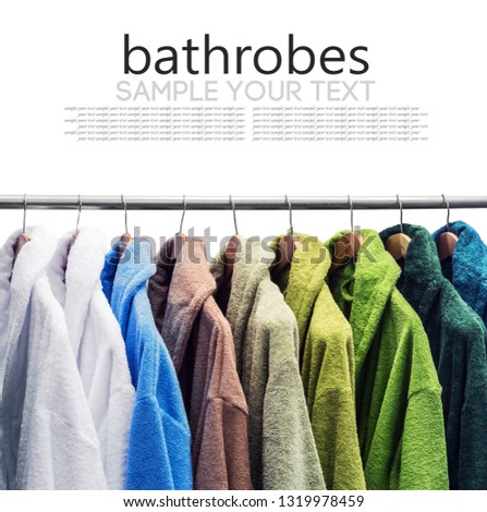 different color bathrobes on the hanger in the shower room, in the store or on the market. isolated on white background. Text delete