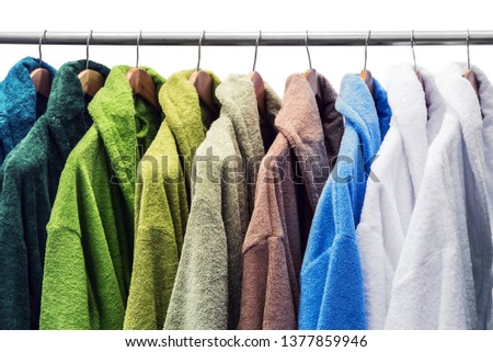 different color bathrobes on the hanger in the shower room, in the store or on the market. isolated on white background