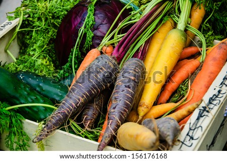 Different color carrots, red cabbage and cucumbers in wooden box. Fresh organic produce from a local farmers market in Paris.