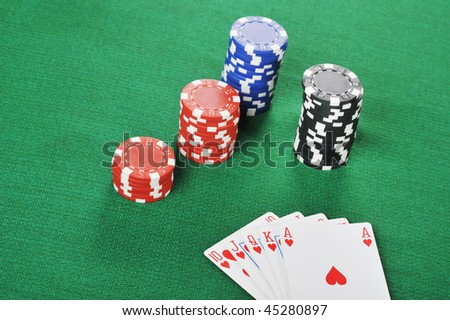 different color chips for gambling and playing cards on green